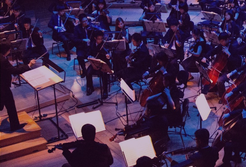 A photo of a symphony orchestra performing from above stage left and the conductor's right shoulder. There is blueish-purple light playing over the musicians, and the conductor's podium seems to glow golden-brown. A cello stands out, glowing bright red among the blue-purple.